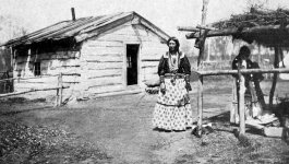 A woman stands in front of a small, run down wooden house.