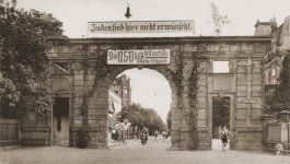View of Nuernberger Tor, one of the entrances to University of Erlangen with a large archway, from which two banners hang.