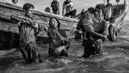A woman and a baby are helped off a boat.
