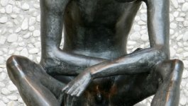 A sculpture of a naked, featureless man sitting with his head lowered in despair.