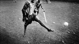 Amputees, some on crutches, play soccer on a rocky field. Circa 2002.