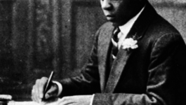 Young, black South African man in a suit writing at a desk.