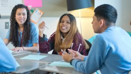 A group of male and female high school students engage in a discussion.