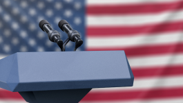 Podium with two microphones in front of the American Flag.