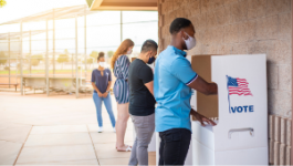 A group of people wearing masks while voting.
