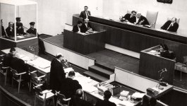 A view of the courtroom during the Eichmann trial. Eichmann is seated behind glass.