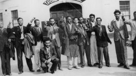 """Group of suited black South African men smiling and gesturing with a """"thumbs-up."""""""