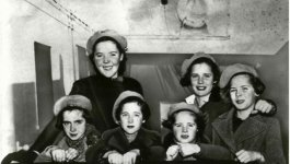 Six girls of varying ages pose together, all wearing wool winter coats and hats.