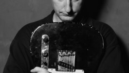 Portrait of Billy Bragg clutching his guitar.