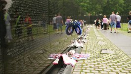 Visitors walk by the Vietnam Veterans monument with flowers and notes left in front of it.