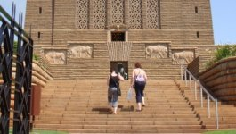 Two women walking up steps to the entrance of a multi-story, square, granite monument that is decorated with four stone reliefs of animals beneath a large decorative arched window.
