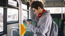 A student stands on a bus while looking at his phone.