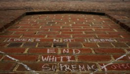 """Image of the side of a brick building that has """"Lovers Not Losers End White Supremacy"""" in white chalk"""