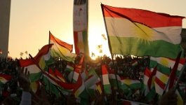 A large group of Kurds wave Kurdish flags with the sun setting behind them.