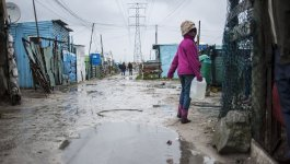 Black South African girl walking with an empty water jug along a wet road lined with poorly-made dwellings.