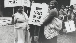 "Group of black South African women protesting and carrying signs that say ""Women do not want passes"" and ""With passes we are slaves"