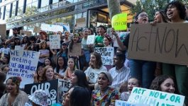 A crowd of young people seated and standing hold up signs at a climate change protest.