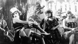 A scene from a film. A young woman is seen from the side, sitting on a barrel with one leg lifted. She wears a cabaret outfit of a sleeveless, short-skirted dress, ruffled undergarments, thigh-high stockings with the garters showing, high heels, and a silk or satin top hat. Other older women in more modest clothing are visible in the background.