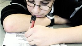 A school-aged boy rests his head on his arm while working on schoolwork.