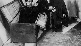 "Still image from the silent expressionist film ""The Cabinet of Dr. Caligari."" In a small room with a small window, a man in a cloak and a top hat stoops over a man rising out of a large chest on the floor."