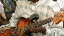 A young Congolese man wearing a plaid button-down shirt sits while playing bass guitar. In the background, men and women wearing colorful clothing sit in several rows. Many women wear headwraps.