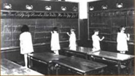 Five students stand at two large chalkboards in a classroom, working on an assignment.