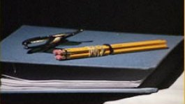 Pencils on top of a blue notebook.