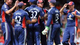 Members of Enland's national cricket team gather on the field to celebrate. The players are of many ethnicities.
