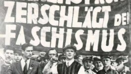 A crowd of men stand beneath a massive banner with German words on it.