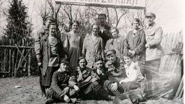 A group of young men and women gather beneath a large banner.