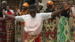 Several black Congolese women dance in bright clothing.