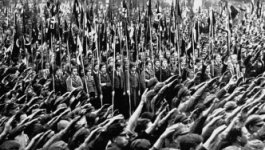 A massive group of Hitler Youth perform the Hitler salute, while some bear the Nazi flag.