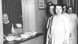 A line of women in long-sleeved, floor-length nightgowns stand in line at a service window where a kitchen worker is stationed to give them a bowl of soup.