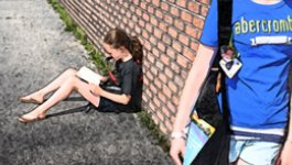 Two school-aged girls talk to each other in the foreground, while another girl sits alone in the background, reading a book.