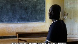 A young black Ugandan man sits at a desk, facing a blank chalkboard in an empty classroom.