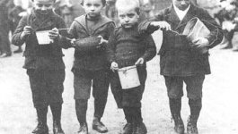Four young boys in  stand outside, eating from a variety of vessels: a small pot, a wide bowl, and two from pails. Circa 1921.