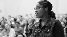 A young woman at the front of an audience holds a microphone.