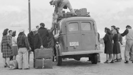 Japanese Americans unload their belongings off a car.
