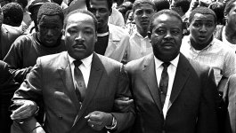 Photo of Martin Luther King, Jr. marching arm in arm with a crowd of men participating in the  1968 Memphis Sanitation Worker's Strike.