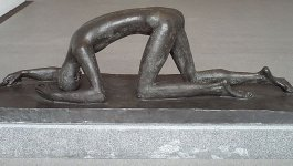 A sculpture of a long, thin man crawling on the ground with his head down.