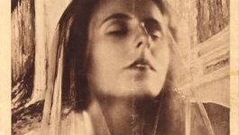 A movie poster for Der heilige Berg (The Holy Mountain, 1926) featuring a woman with a sheer scarf over her face and closed eyes.