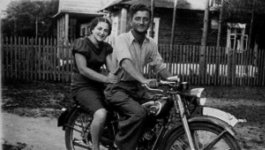 A man and woman sit on a motorcycle in pre-World War II era Europe.