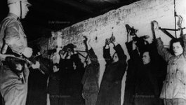 Nazi soldier with a gun pointed at a line of people with their hands in the air standing against a wall. Teaser image for history lesson on dismantling democracy