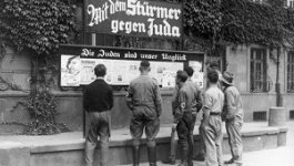 A group of men stare at a propaganda poster.