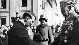 Adolf Hitler stands with two Nazi German soldiers.