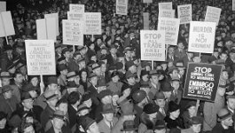 A crowd of American men and women hold signs protesting Nazi Germany's actions.