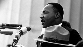 Dr. Martin Luther King, Jr. stands at a microphone giving a speech to a crowd.