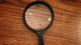 Magnifying glass on wooden table.
