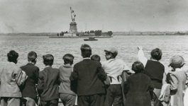 A group of children in 1930s era clothing stare and point at the Statue of Liberty.