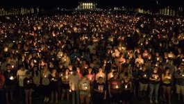 A group of people at a candlelight vigil